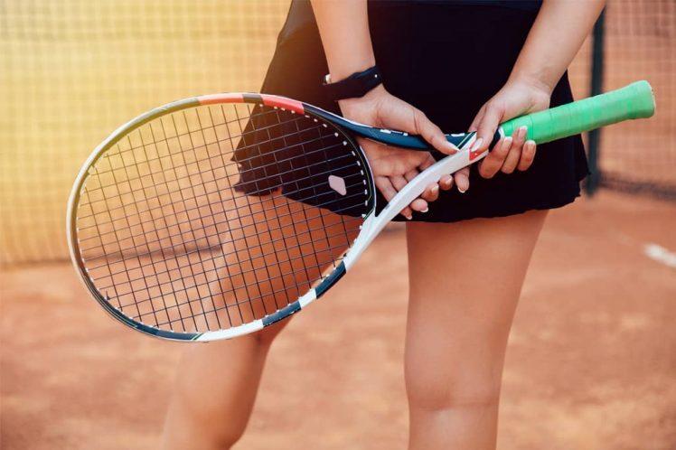 Jugadora profesional de tenis sosteniendo raqueta de competición